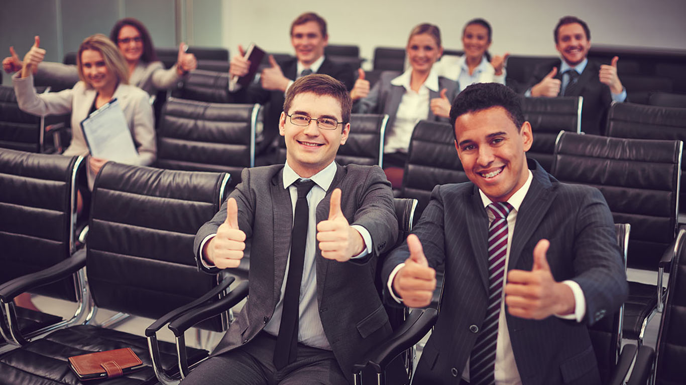 Two happy young businessmen showing thumbs up on background of their colleagues